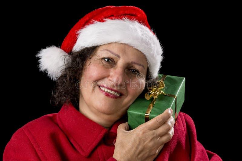 Signora senior con Santa Claus Hat ed il regalo avvolto immagine stock libera da diritti