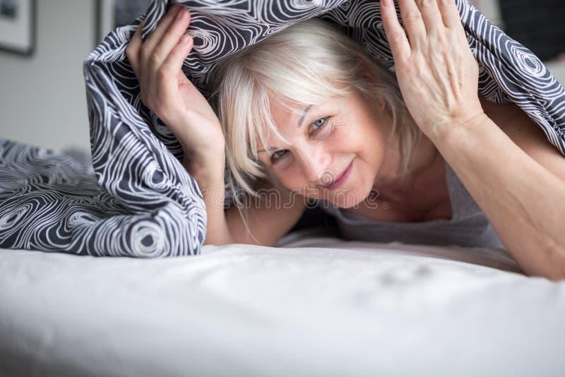 Signora senior felice che si nasconde sotto la trapunta sul letto fotografia stock
