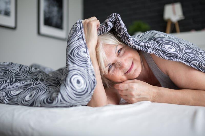 Signora senior felice che si trova sul letto sotto la trapunta immagini stock libere da diritti