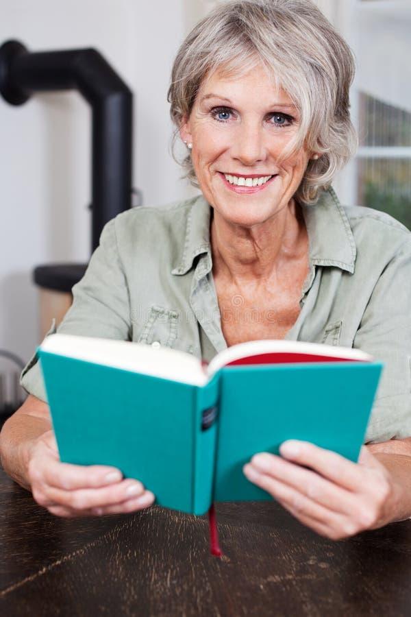 Signora senior moderna che legge un libro immagini stock libere da diritti