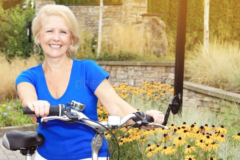 Signora senior su una bici immagini stock