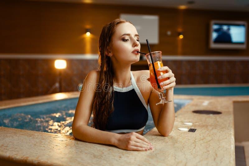 Signora sexy beve il cocktail di frutta sul lato dello stagno immagini stock