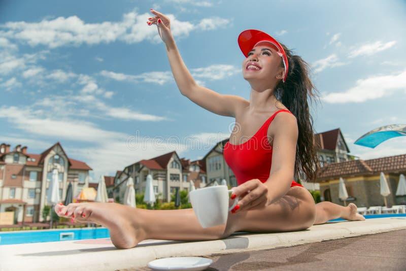 Signora sexy dallo stagno in un costume da bagno rosso con una tazza di caffè Prendendo il sole dal raggruppamento immagine stock libera da diritti