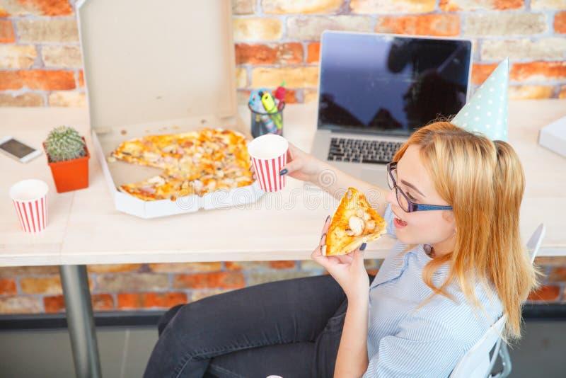 Signora sorridente dell'ufficio, ad ora di pranzo ed alla pizza di cibo Atmosfera festiva fotografia stock libera da diritti