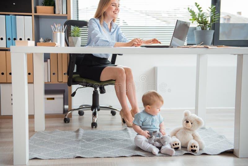 Signora sorridente e bambino calmo in ufficio fotografia stock