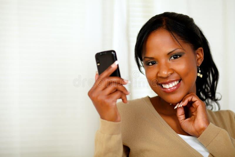 Signora specializzata che legge un messaggio sul cellulare fotografia stock libera da diritti