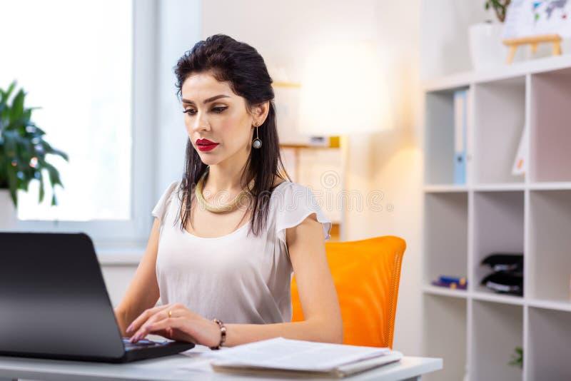 Signora supplichevole dai capelli lunghi nel funzionamento superiore bianco sul computer portatile fotografia stock libera da diritti