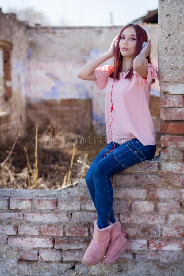 Signora sveglia delle testarosse che ascolta la musica in cuffie sulle rovine mura i mattoni rossi di retro casa fotografia stock