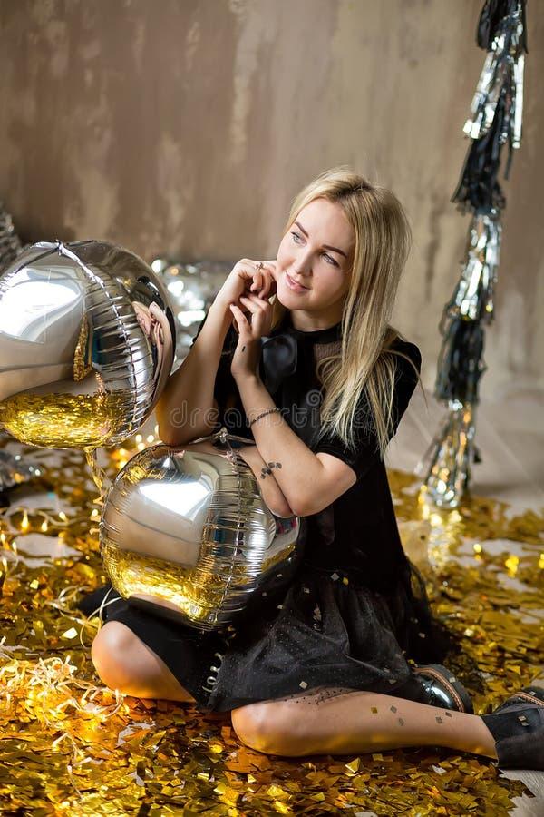 Signora sveglia stupefacente che celebra la festa di compleanno del nuovo anno, posando nel fondo di lustro dell'oro e gettante i immagine stock