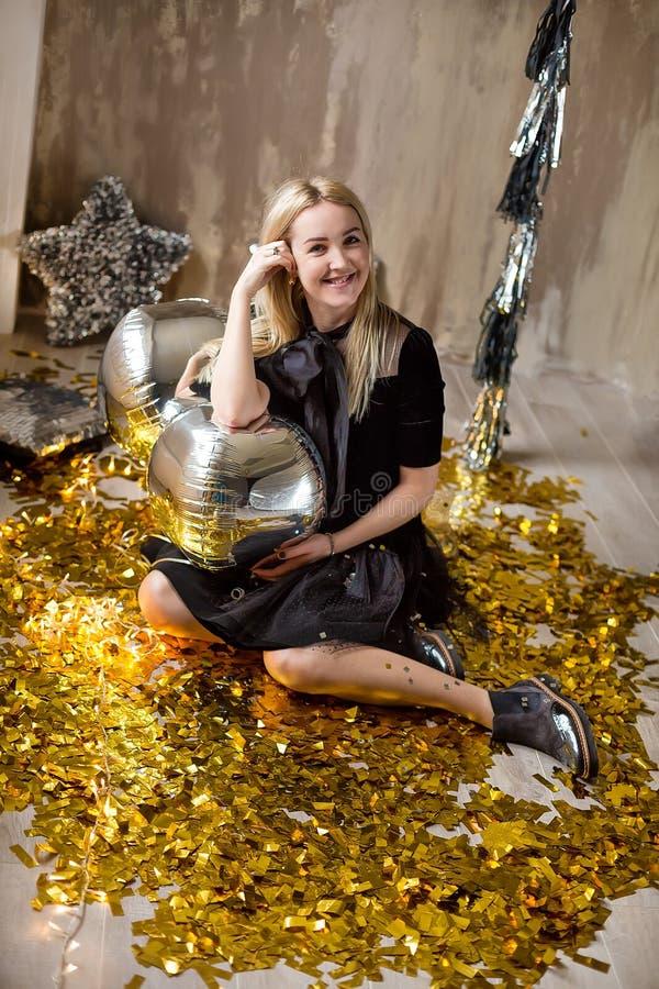 Signora sveglia stupefacente che celebra la festa di compleanno del nuovo anno, posando nel fondo di lustro dell'oro e gettante i immagini stock