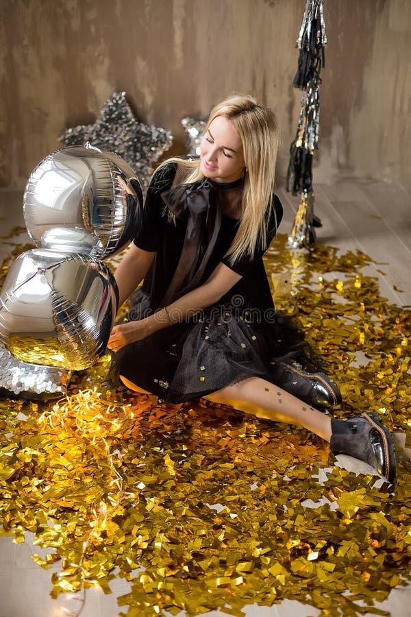 Signora sveglia stupefacente che celebra la festa di compleanno del nuovo anno, posando nel fondo di lustro dell'oro e gettante i immagini stock libere da diritti