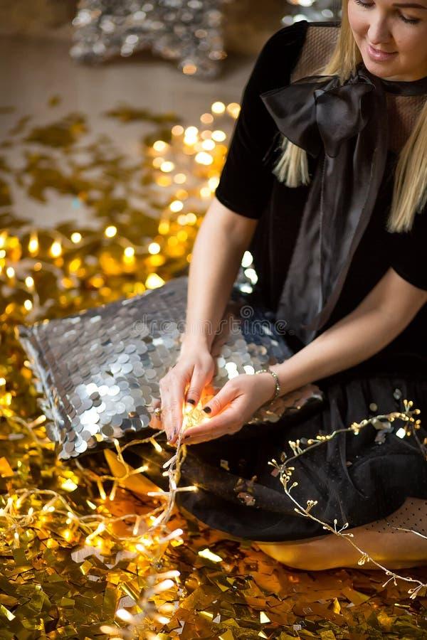 Signora sveglia stupefacente che celebra la festa di compleanno del nuovo anno, posando nel fondo di lustro dell'oro e gettante i fotografia stock libera da diritti