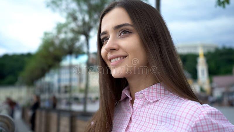 Signora teenager graziosa che sorride nel centro urbano, fare un giro turistico delle attrazioni, turismo fotografia stock libera da diritti