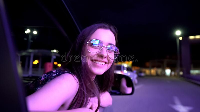 Signora ubriaca spensierata che attacca la testa dall'automobile, movente a casa dopo il partito si diverte immagini stock