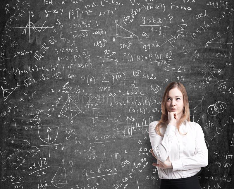 Signora in vestiti convenzionali che pensa alle soluzioni possibili dei problemi quantitativi Le formule di per la matematica son immagine stock