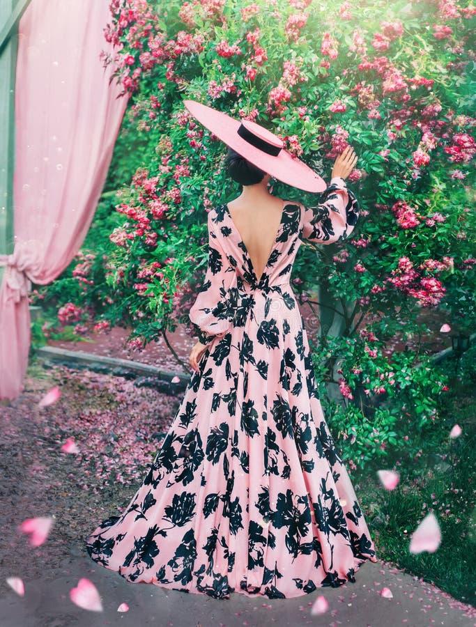 Signora in vestito rosa lungo con i modelli neri Donna nell'ultima cosa in cappelli immagine stock
