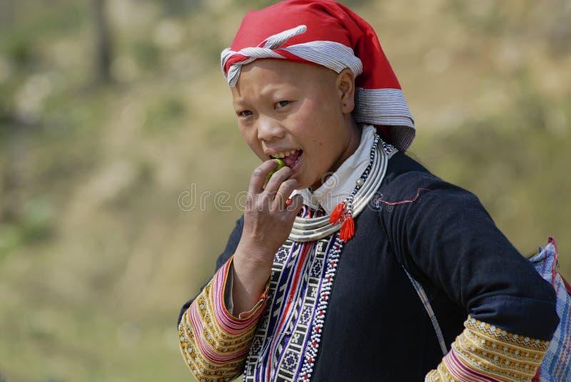 Signora in vestito rosso tradizionale dalla tribù della collina di Dzao mangia la frutta in Sapa, Vietnam immagine stock libera da diritti
