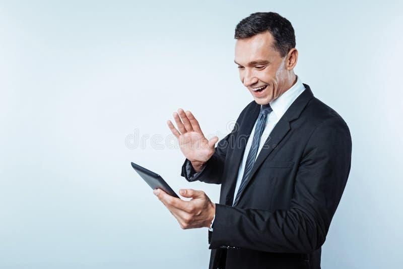 Signore occupato di positivo che ha video chiamata sulla compressa digitale fotografie stock