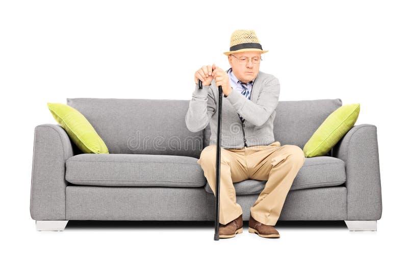 Signore senior preoccupato che si siede su un sofà immagine stock libera da diritti