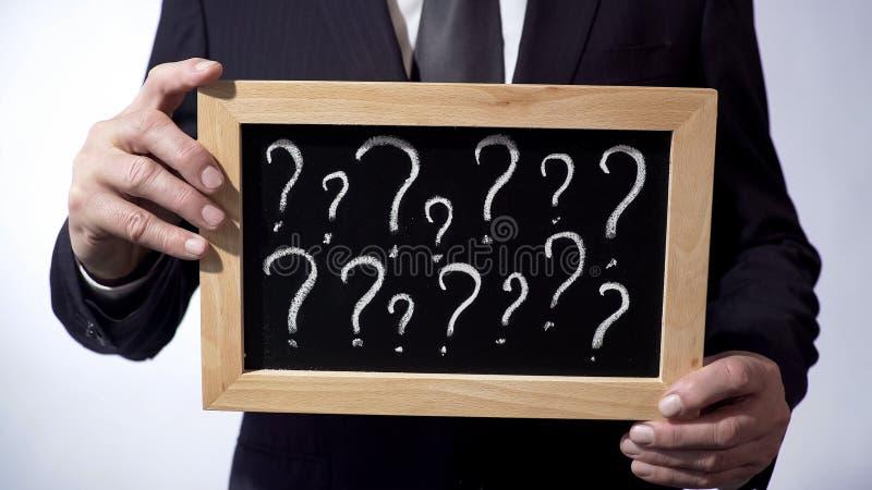 Signos de interrogación escritos en la pizarra, varón que lleva el traje clásico que lleva a cabo una muestra fotografía de archivo libre de regalías