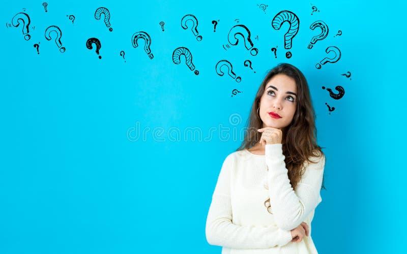 Signos de interrogaci?n con la mujer joven imagen de archivo libre de regalías