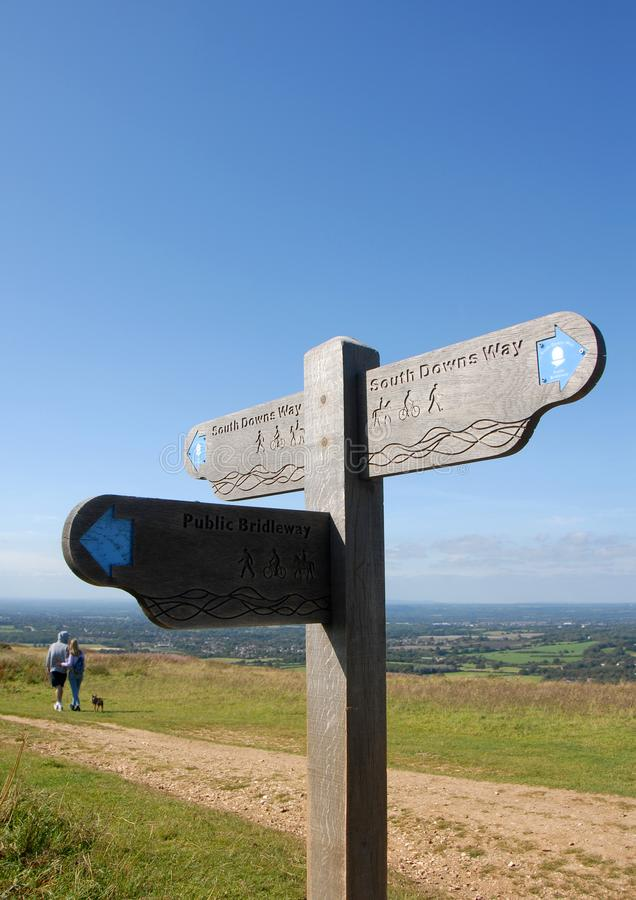 A signpost and a couple walking with a dog on the South Downs Way near Brighton in Sussex, England, UK. South Downs National Park, Sussex, England, UK. A man and royalty free stock photo