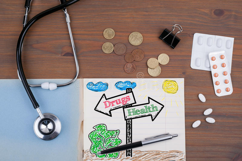 Signpost with Drugs Health text. Doctor's desk with notebook.  stock images