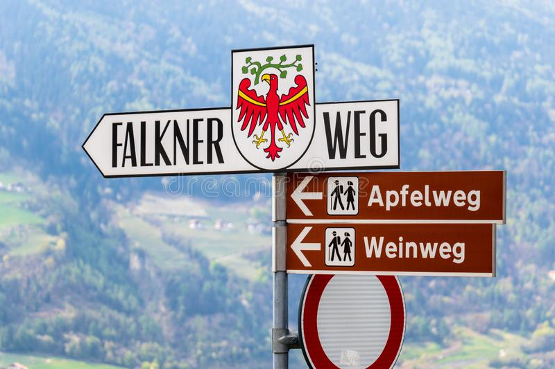 Signpost guiding to famous Falconer Road, in german, Falkner Weg, in Village Tyrol, Mountains Landscape in the background. Signpost guiding to famous Falconer stock images