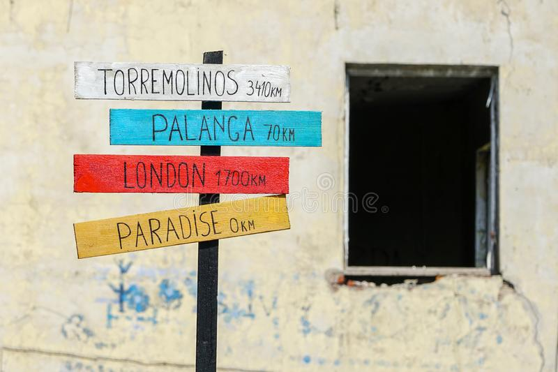 Signpost with plates with inscriptions about the distances to different cities and paradise. Signpost with colored plates with inscriptions about the distances royalty free stock photography