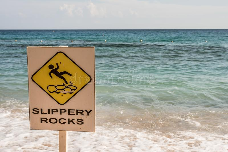 Signpost slippery rocks at the beach stock photos