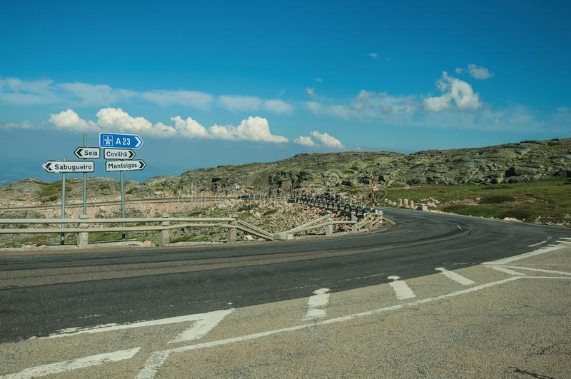 Signposts with town directions on road crossing rocky landscape. And bush fields, at the highlands of the Serra da Estrela. The highest mountain range in stock image