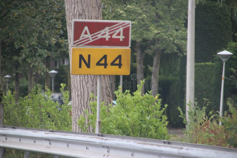 Signs along the motorway in Wassenaar that motorway A44 stops and will continue as regional road N44 in the Netherlands.  royalty free stock photography