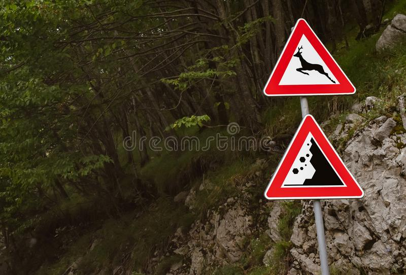 Warning signs in mountain road. Signs danger wild animals and landslide on the mountains road stock photos