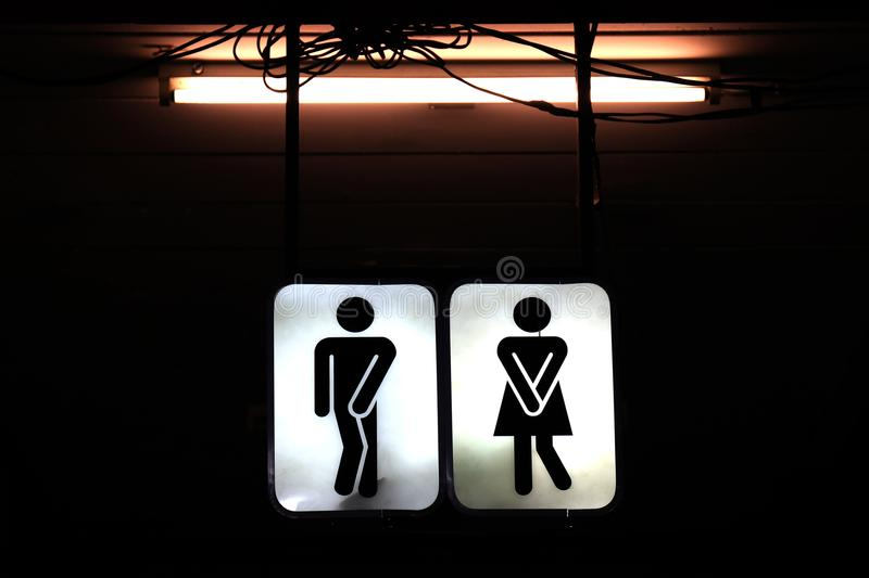 Signs night bathroom, old toilet symbol male and female in the night background stock photo