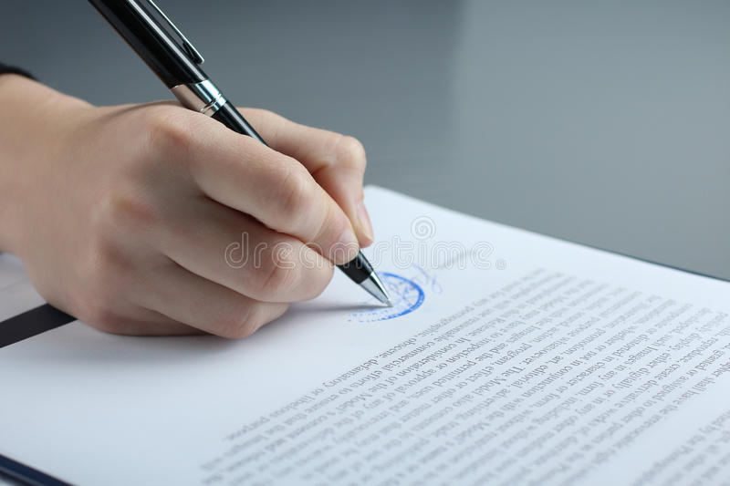 Signs papers. Male businessman`s hand signs papers royalty free stock photography