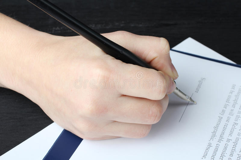 Signs papers. Male businessman`s hand signs papers stock photo