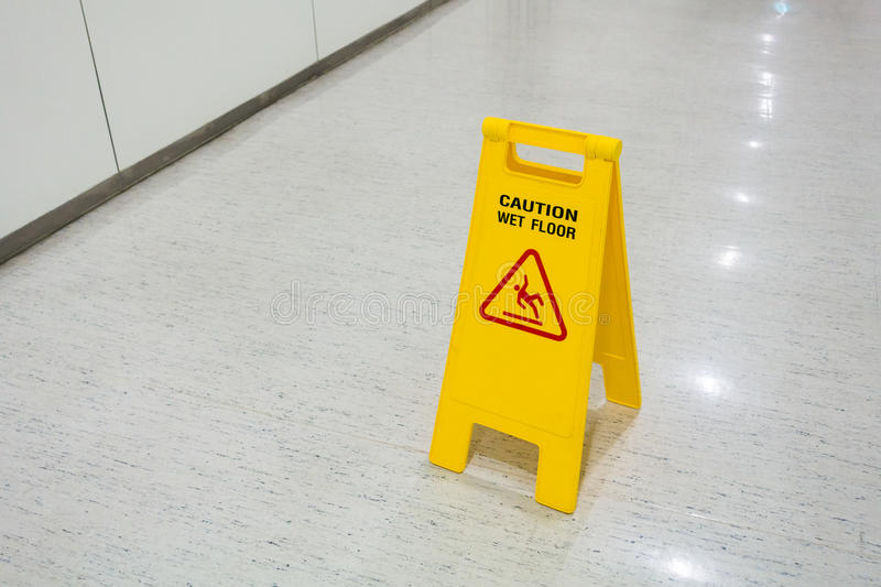 Signs plastic yellow put on floor text caution wet floor royalty free stock photography