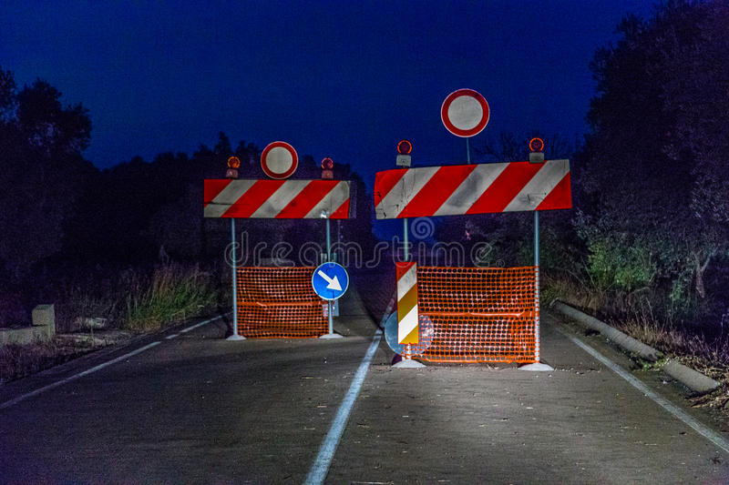 Signs prohibiting access. To a interrupted road illuminated by the headlights of a car at night royalty free stock photography