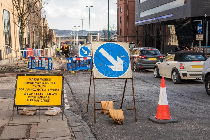 Signs and Traffic Cone at a Roadworks Site. Signs, Barriers and Traffic Cones Blocking a Lane on a Busy Street in a City Centre Because of Roadworks in Progress stock images