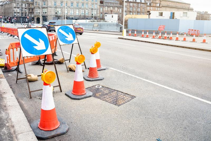 Signs and traffic cones at the beginning of a construction site along a wide urban road. Signs and traffic cones indicating the closure of a lane of a wide urban stock photos