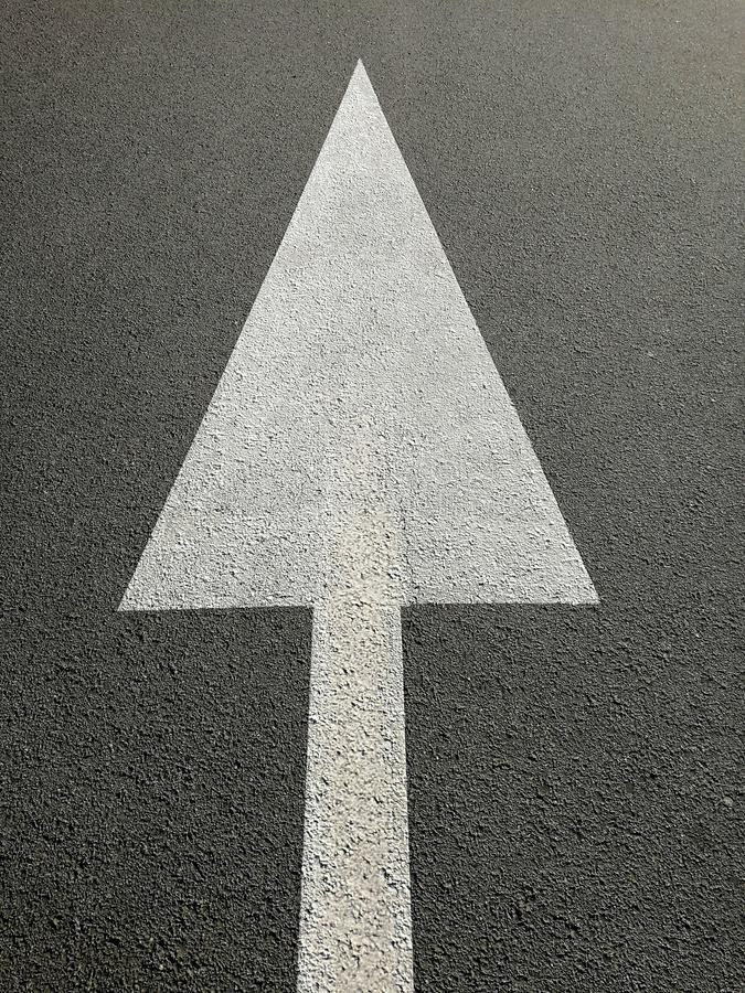 Signs with white arrow on the asphalt. As abstract concept of direction stock photo