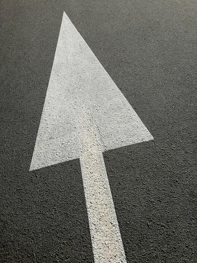 Signs with white arrow on the asphalt. As abstract concept of direction royalty free stock photos