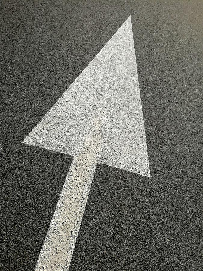 Signs with white arrow on the asphalt. As abstract concept of direction royalty free stock image