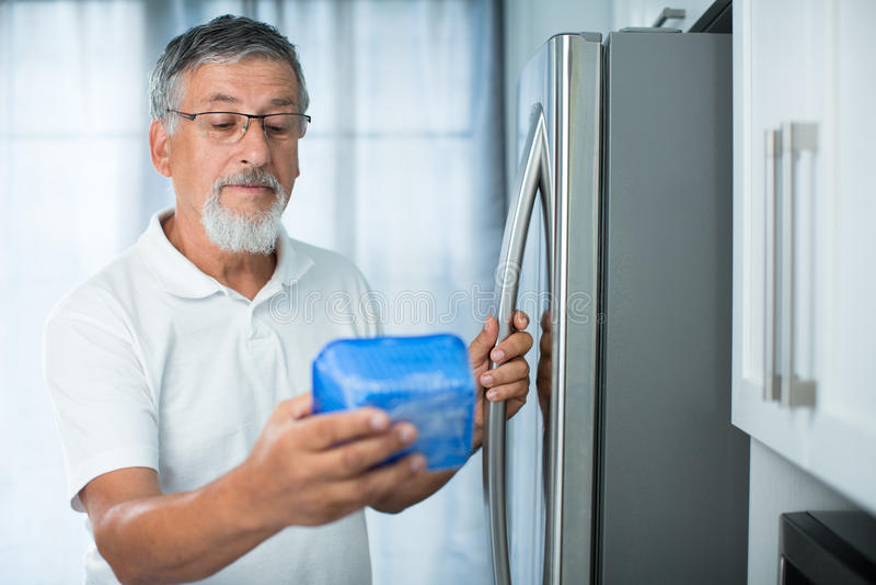 ¿Sigue siendo esto fino? Hombre mayor en su cocina imagenes de archivo