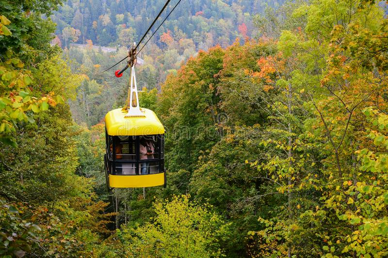 Sigulda cable car for traveling through the Gauja valley, Latvia. Panoramic view of leaf fall forest. Autumn landscape on cool,. Cloudy day stock photo