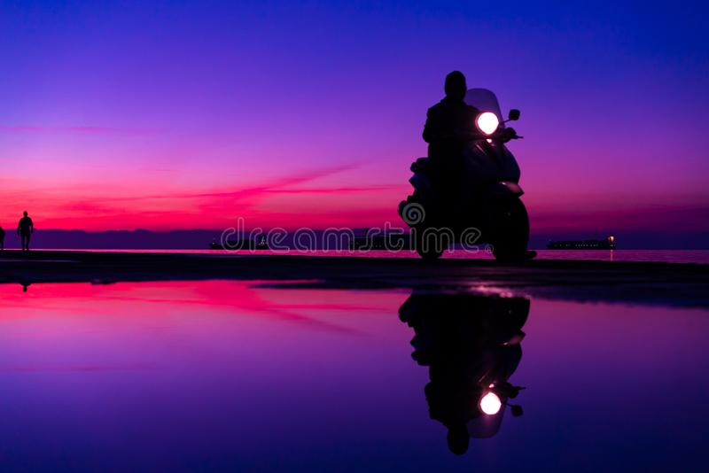 Sihouette of Man with a motorbike; riding by the Sea; against be stock image
