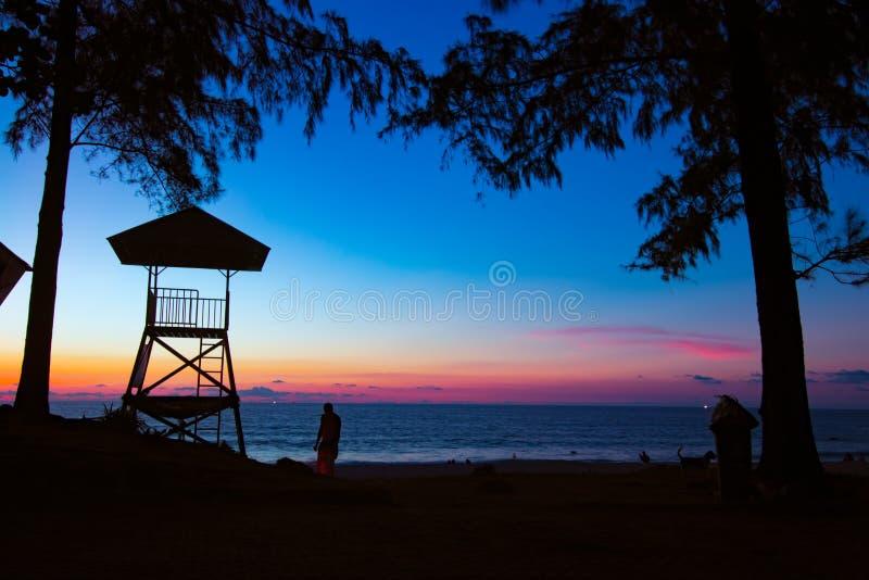 Sihouette man på strand- och sucuritykojan royaltyfri bild