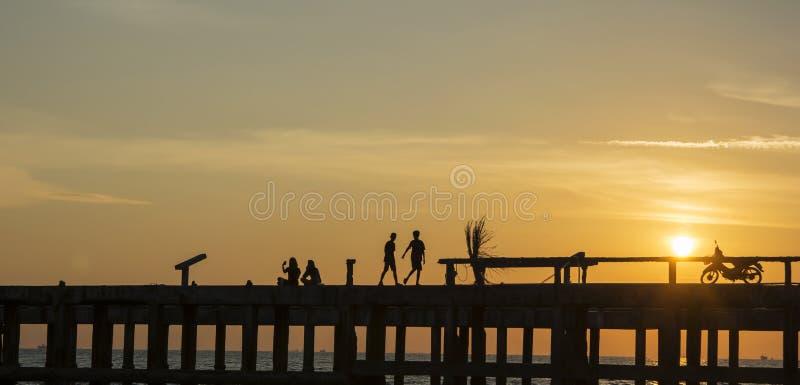 Sihouette sikt av avkoppling på stranden royaltyfri foto
