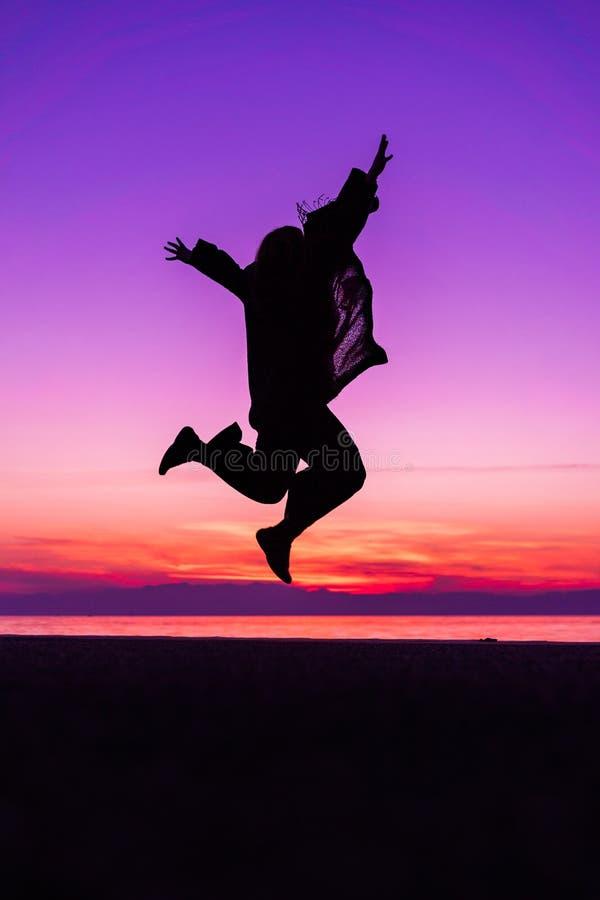 Sihouette Szczęśliwy kobiety doskakiwanie z radością, przeciw pięknemu af zdjęcie stock