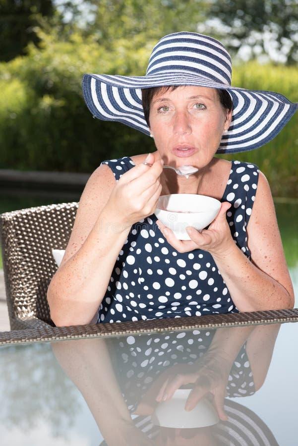 siiting由水池和吃一碗果子的可爱的妇女 免版税库存照片